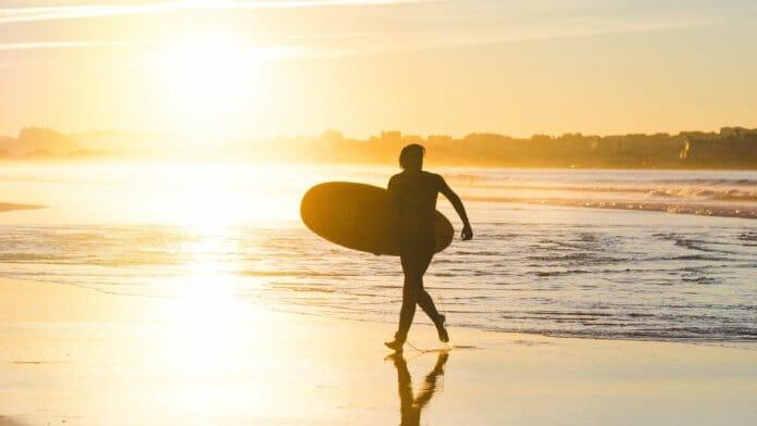 Mit Board am Strand laufender Surfer: Typischer Sport im Sommer