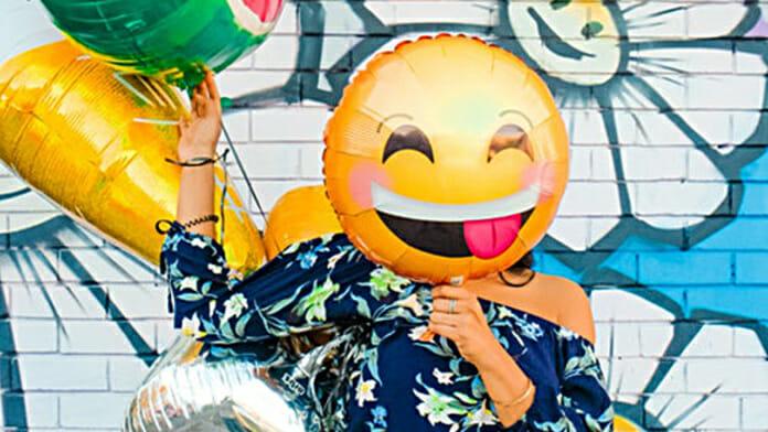 Was passiert im Körper, wenn wir lachen? (Junge mit mit vor dem Gesicht gehaltenen Smiley-Luftballon