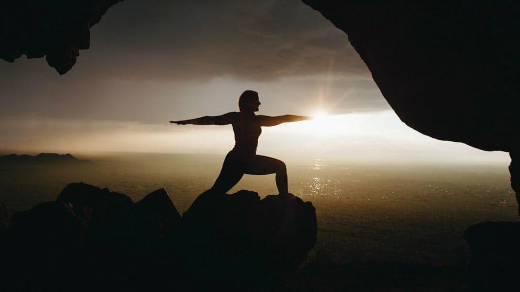 Yoga während des Sonnenaufgangs auf einem Berg