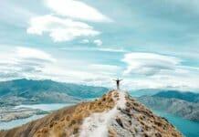 Person auf einem Berggipfel, die motiviert die Arme nach oben reißt