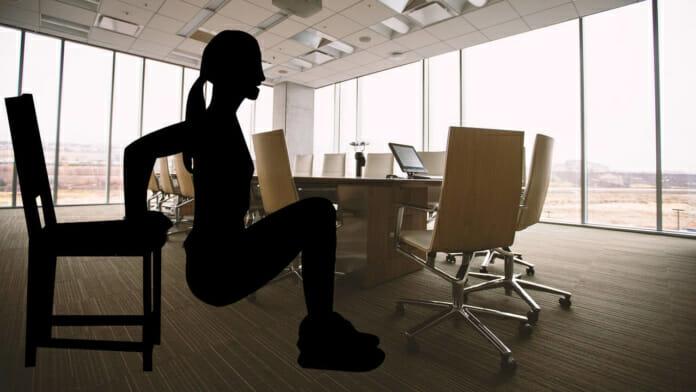 Frau beim Dip Training auf einem Stuhl - Im Hintergrund Roundtable am Arbeitsplatz