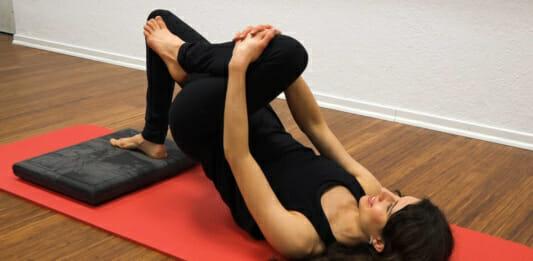 Fitnesstrainerin beim Training liegend auf einer Matte