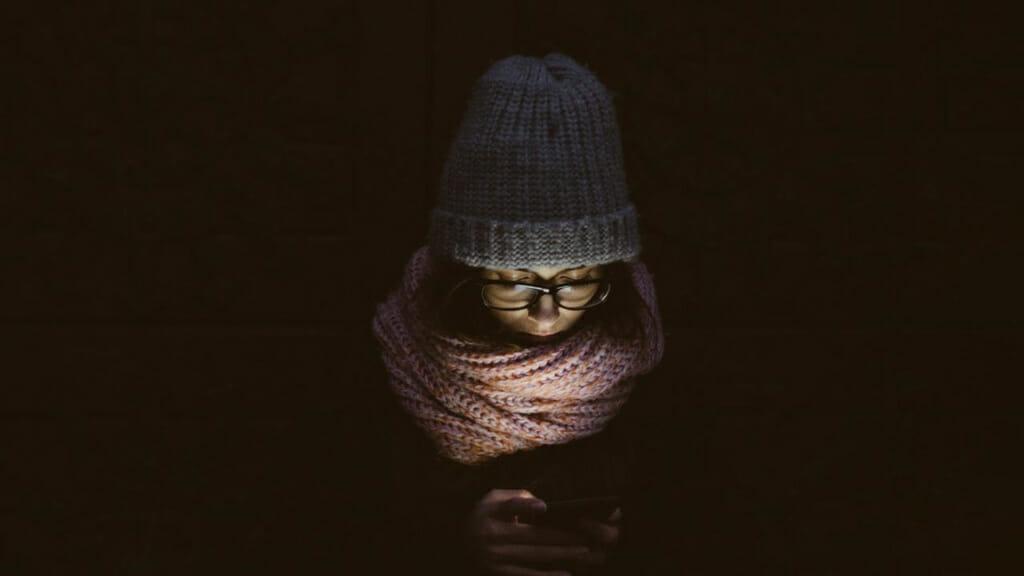 Deprimiert auf den Boden schauende Person in der Dunkelheit