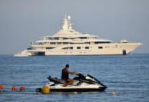 Mann mit kleinem Boot beobachtet große Yacht