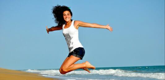 Lebensfrohe junge Frau am Strand