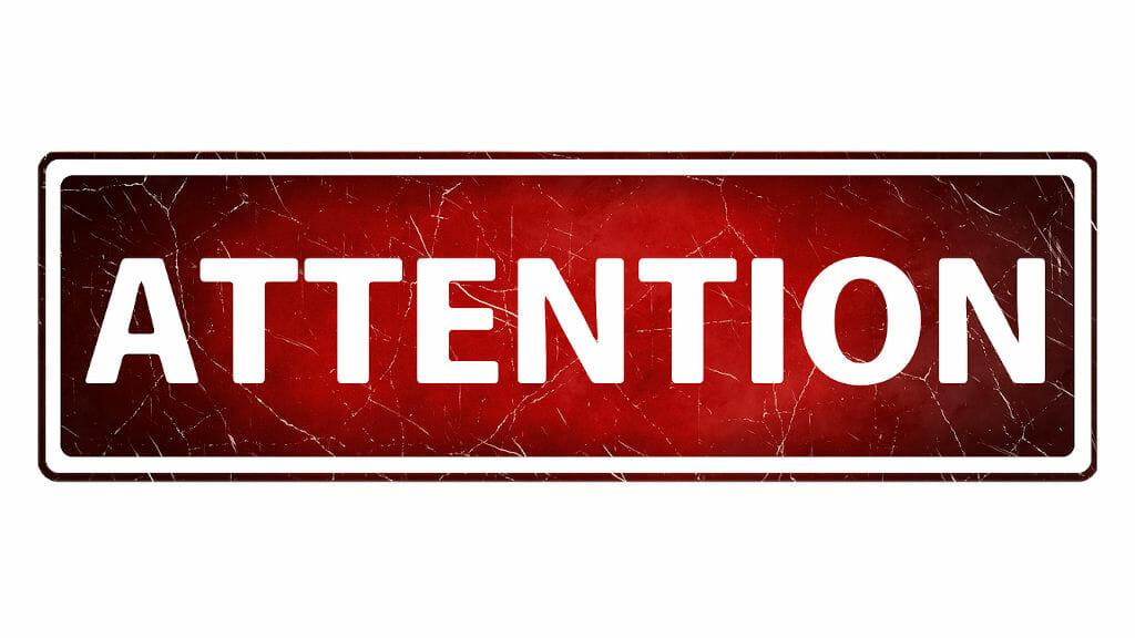 """Schriftzug """"attention"""" auf rotem Hintergrund"""