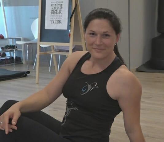 Sabine Kunze auf dem Boden sitzend im Trainingsraum