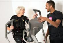 Frau beim EMS Training auf dem Crosstrainer unter den wachsamen Augen eines Trainers