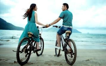 Liebespaar mit Fahrrad am Meer