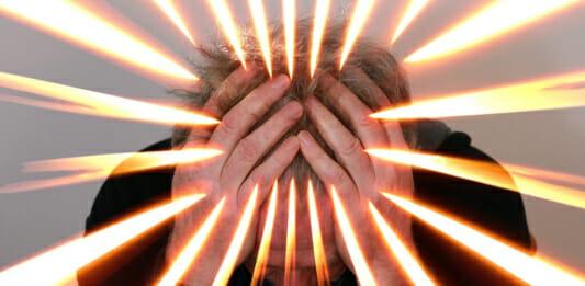Gestresste Person, die ihre Hände über dem Kopf zusammenschlägt
