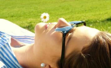 Frau mit Gänseblümchen im MUnd, entspannt auf einer grünen Wiese liegend
