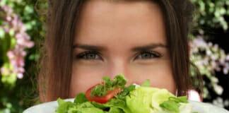 Junge Frau, die einen Teller mit Rohkostsalat präsentiert