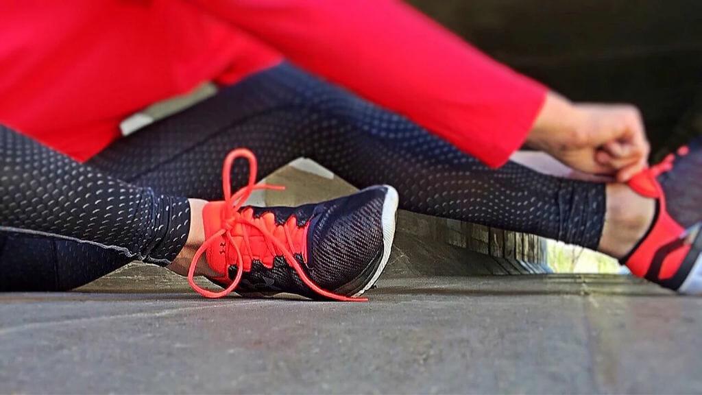 Sportler*in sitzend auf dem Boden schnürt sich die Sportschuhe