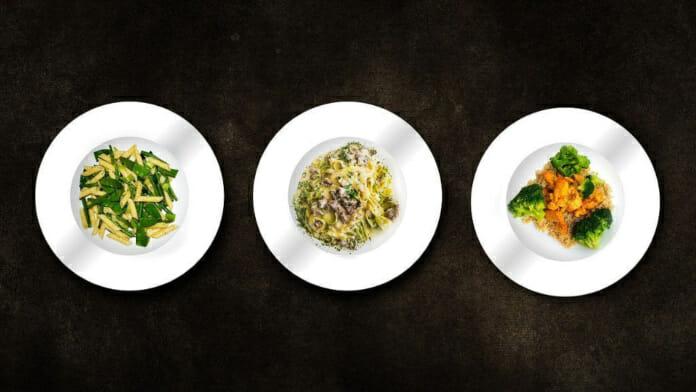 Drei Teller mit je einer Mahlzeit präsentiert auf schwarzem Hintergrund