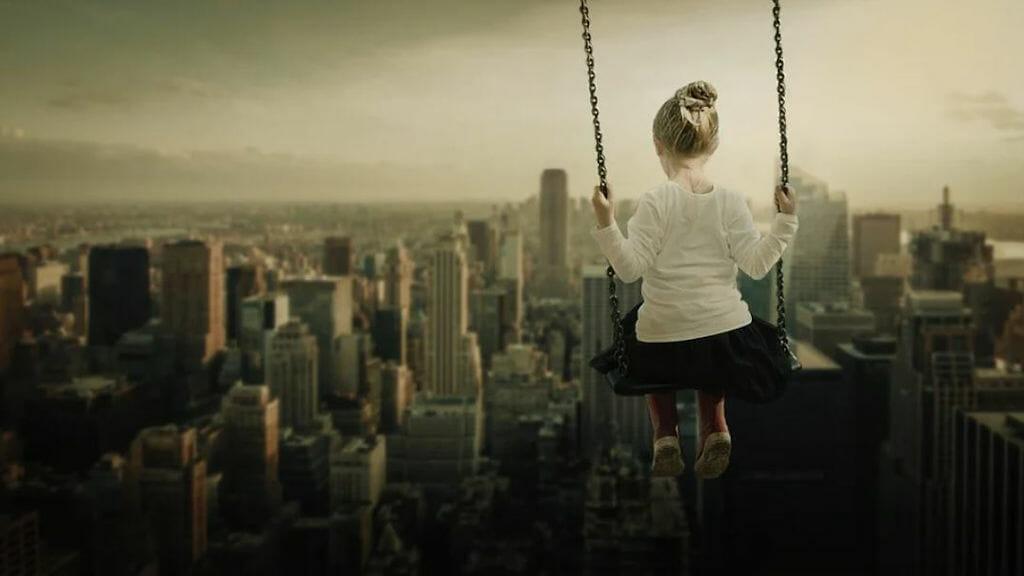 Lass Deine Träume wahr werden: Hoch schaukelndes Kind mit Blick auf die New Yorker Skyline