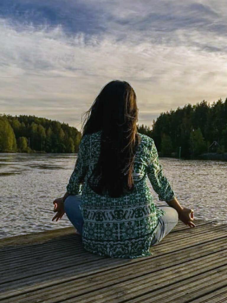 Junge Frau beim Meditieren am Seeufer