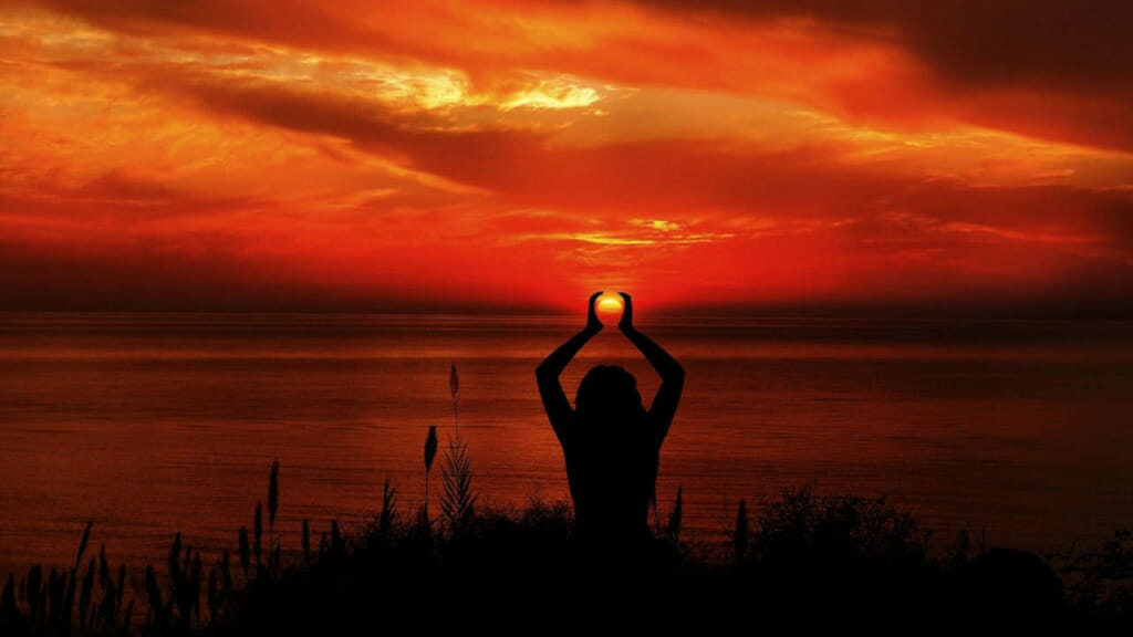 Frau beim Yoga während des Sonnenuntergangs. Online Fitness wird zum Erlebnis