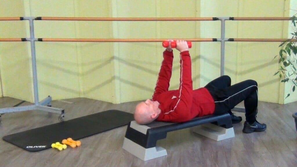 Trainierender in liegender Position auf dem Reebok Step bei den Hantel Übungen für den Brustmuskel (Startposition der Bewegung)