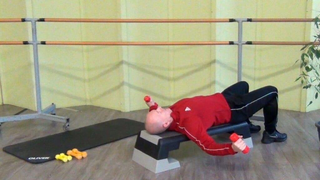 Trainierender in liegender Position auf dem Reebok Step bei den Hantel Übungen für den Brustmuskel (ndposition der Bewegung)