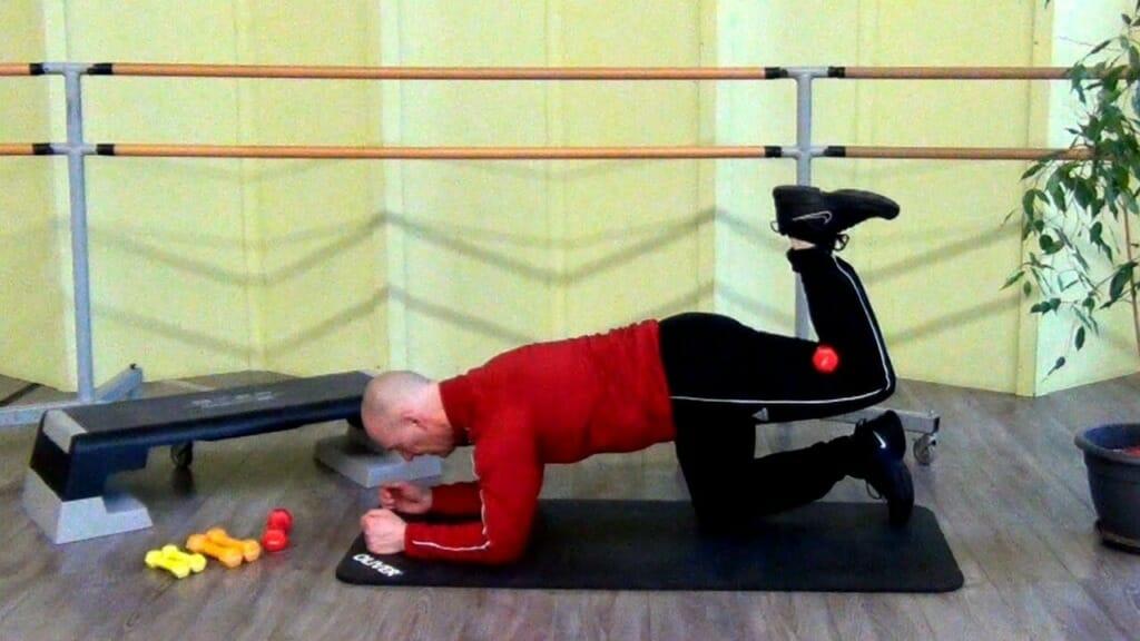 Trainierender im Vierfüßlerstand bei den Hantel Übungen für den Po (Startposition der Bewegung)