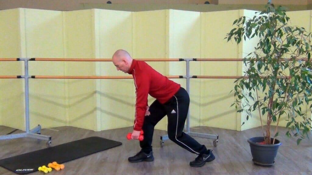 Trainierender in stehender, leicht vorgebeugter Position bei den Hantel Übungen für den Rücken (Startposition der Bewegung)