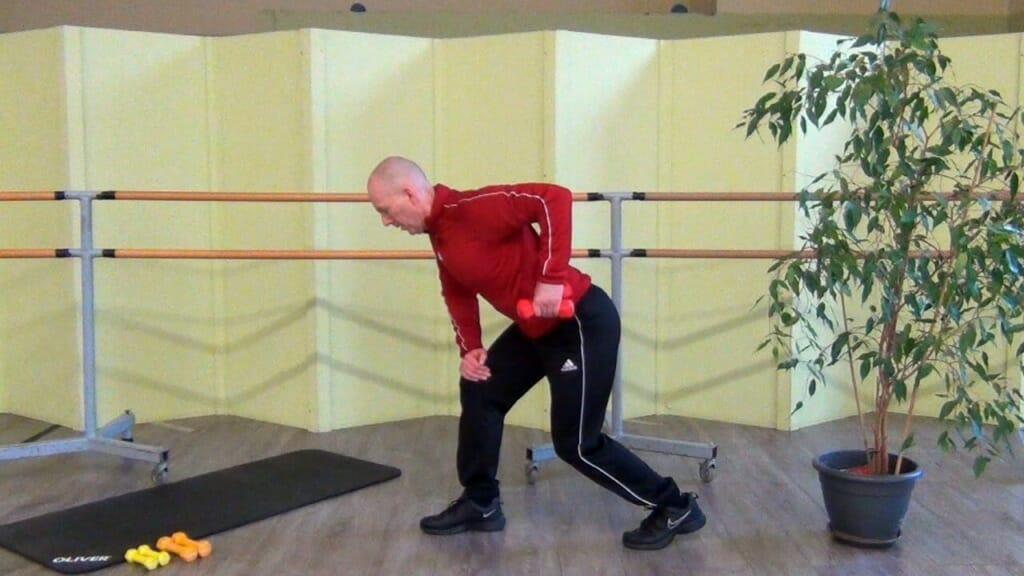 Trainierender in stehender, leicht vorgebeugter Position bei den Hantel Übungen für den Rücken (Endposition der Bewegung)