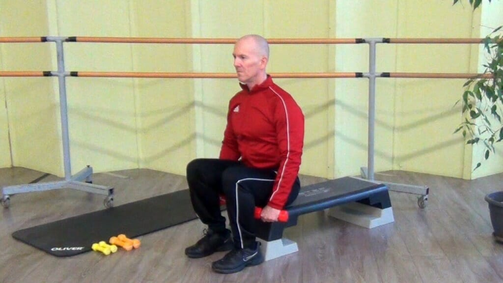 Trainierender in sitzender Position bei den Hantel Übungen für die Schultern (Anfangsposition der Bewegung)