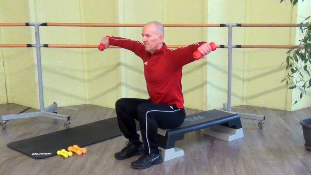 Trainierender in sitzender Position bei den Hantel Übungen für die Schultern (Endposition der Bewegung)