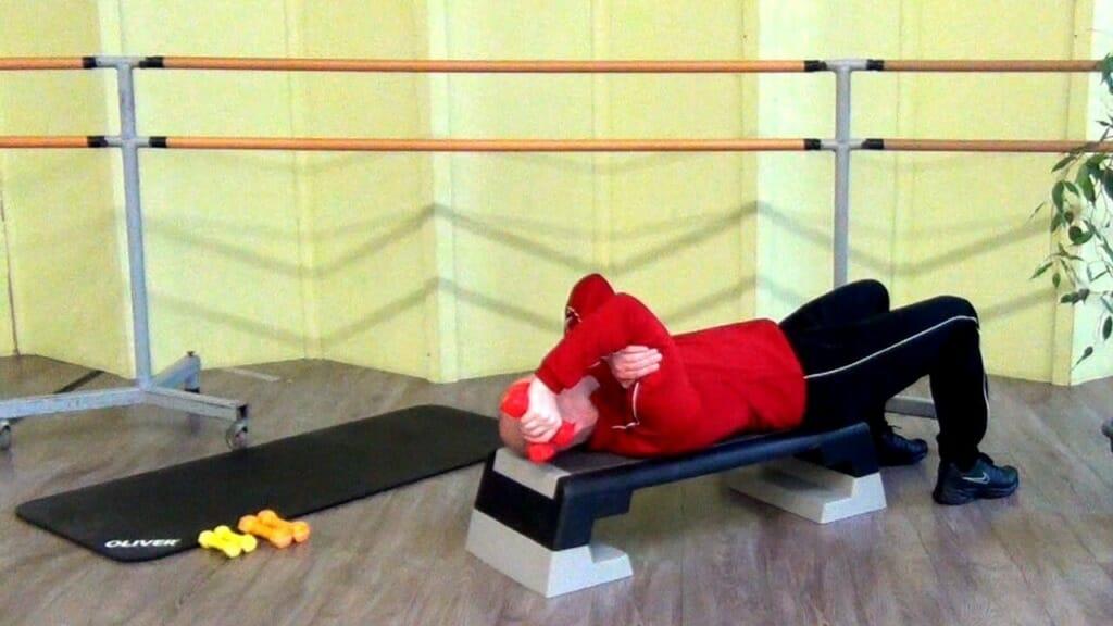 Trainierender in Rückenlage, bei den Hantel Übungen für den Trizep (Anfangsposition)
