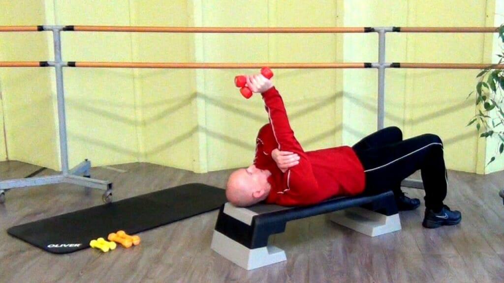 Trainierender in Rückenlage, bei den Hantel Übungen für den Trizep (Endposition)