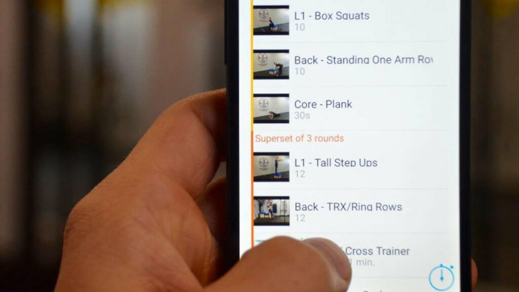 Trainierender prüft die Vorgaben seines Online Kurses auf dem Handy