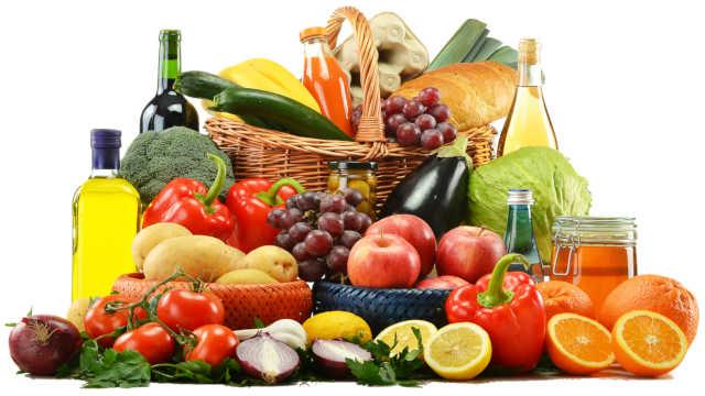 Bunt gemischter Korb mit gesunden Lebensmitteln: Obst, Gemüse, Öle und Getreideprodukte