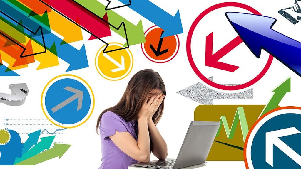 Stress am Arbeitsplatz: Frau am Schreibtisch vor ihrem Laptop sitzend. Sie hält die Hände vor ihr Gesicht.