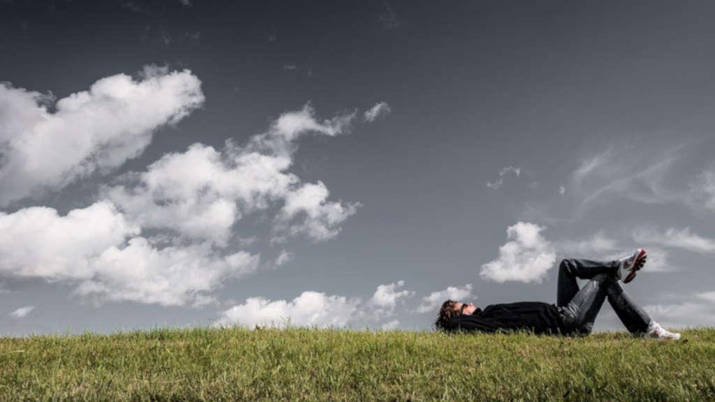 Entspannungstechniken ganz einfach: Mann liegt relaxed im Gras
