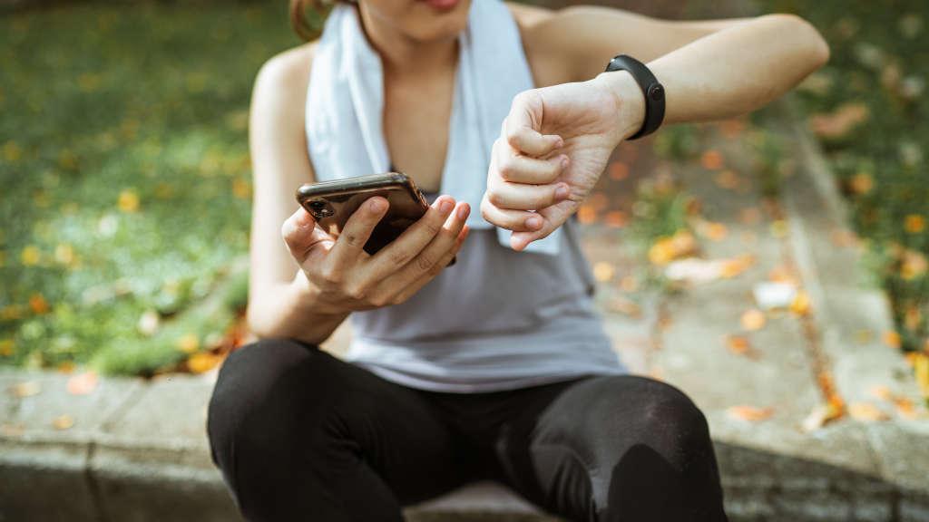 Junge Frau sitzend beim prüfen ihrer Fitness App