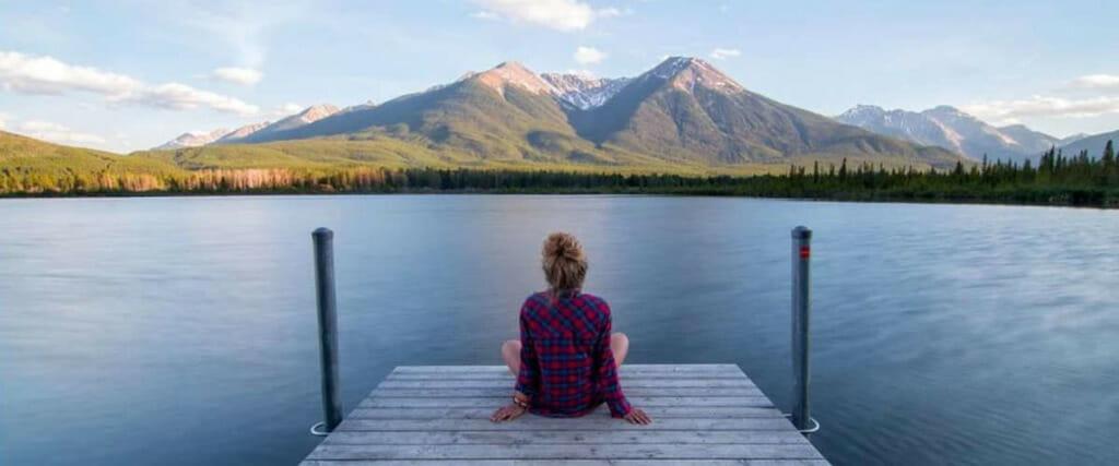 Entspannnungstechniken sind auch in der freien Natur herorragend umzusetzen. Im Bild: Frau auf einem Steg sitzend mit Blick auf einen See und Bergen am Horizont